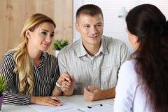 设法年轻家庭的夫妇得到贷款 库存照片