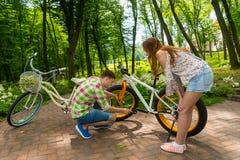 设法年轻的人修理自行车 免版税库存图片