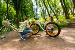 设法年轻的夫妇修理自行车 免版税库存照片