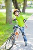 设法年轻的男孩骑自行车 免版税库存照片