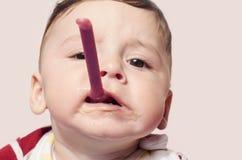 设法滑稽的孩子哺养自己拿着在嘴的婴儿食品匙子 免版税库存照片