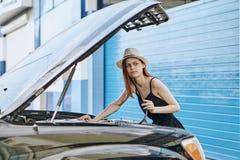 设法年轻美丽的妇女修理在街道上的一辆汽车 免版税库存照片