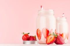 设置两在行家瓶子的新鲜的冷的奶昔用被切的成熟莓果,在高雅桃红色厨房内部的镶边秸杆 免版税库存照片