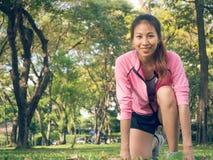 设置准备好的标记的亚裔少妇跑步的锻炼加强她的在玻璃的身体在温暖的轻的早晨 免版税库存图片