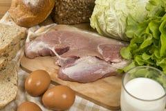 设置包括面包、牛奶、猪肉、鸡蛋和菜在木桌背景的产品 库存图片
