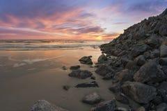 在一个多岩石的海滩的日落 免版税库存照片