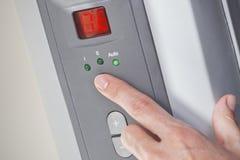 设置在一个数字式可编程序的机油预热器的妇女的手室温 免版税库存图片