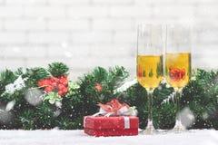 设置在多雪的ta的一个红色礼物盒旁边的两块香槟玻璃 免版税库存图片