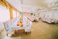 设置在橙色颜色的桌的图象在豪华婚礼大厅 免版税库存图片