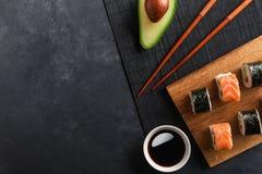 设置寿司和maki卷用切的鲕梨在石桌上 免版税库存图片