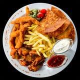 设置用不同的快餐和调味汁在一块白色板材在黑暗的ba 库存照片