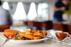 设置用不同的快餐和调味汁在一块白色板材在resta 免版税库存图片