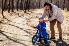 设置盖帽的父亲对他的蓝色连衫裤的小孩儿子在公园 孩子坐一辆蓝色平衡自行车 图库摄影