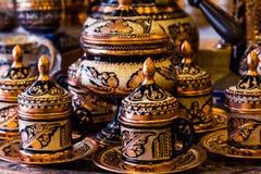 设置美丽的咖啡杯和罐有金黄传统东部装饰品的 库存图片
