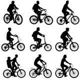 设置骑自行车者男性和女性的剪影 免版税库存图片