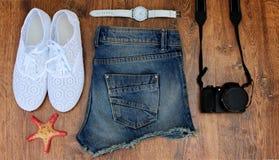 设置去的衣裳海:牛仔裤短缺,运动鞋,手表, photocamera,壳,木背景一张顶视图  库存照片