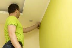 建设者安装塑料造型到天花板和墙壁 免版税图库摄影