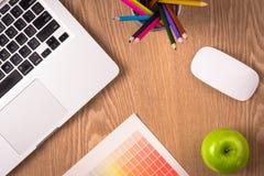 设计与膝上型计算机、颜色铅笔和调色板纸的桌 免版税图库摄影