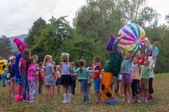 设计卡通者在Kamennomostskiy村庄的宗教节日招待孩子在秋天公园 库存照片