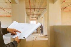 设计在纸计划图纸的手指点在检查大厦技术员位置建造场所与拷贝空间的墙壁内部 免版税图库摄影