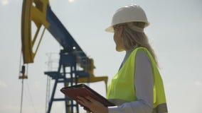 设计女性她成功的工作满意的协调员监督的石油设施画象使用片剂个人计算机- 影视素材