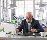 设计工作的高级工程师在建筑师演播室 库存图片