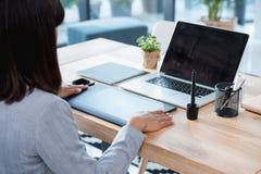 设计师与图画片剂和膝上型计算机一起使用在办公室 库存图片