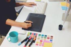 设计师与数字式片剂和便携式计算机一起使用在书桌 免版税图库摄影