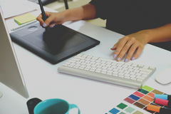 设计师与数字式片剂和便携式计算机一起使用在书桌 库存图片
