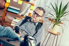 设计师在他的拿着老照相机的办公室 免版税库存照片