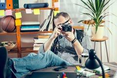 设计师在他的拿着老照相机的办公室 库存图片