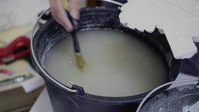 设计师弄湿在一个桶的刷子水并且弄湿灰泥细节与刷子 完成apa的过程 影视素材