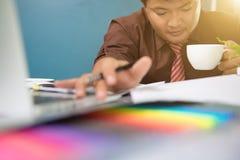 设计师手与便携式计算机一起使用和巧妙的电话和d 图库摄影