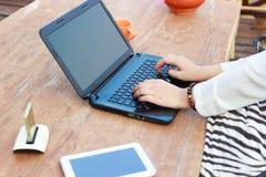 设计师手与数字式膝上型计算机和片剂一起使用在木 免版税图库摄影