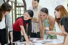设计师概念:工作在时装模特附近的时装设计师  免版税图库摄影