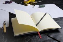 设计师的笔记本特写镜头在桌上的 设计师工具在工作期间的 创造衣裳汇集的概念 免版税库存图片