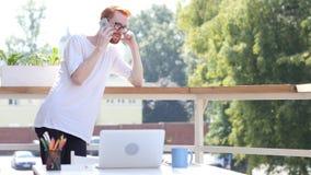 设计师谈话在智能手机,站立在室外的阳台上 免版税库存图片