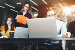 设计师队坐在一张木桌上在一个现代办公室和 免版税库存图片