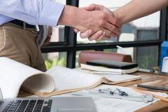 设计成功的成交的握手在建筑计划 A 免版税库存照片