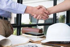 设计成功的成交的握手在建筑计划 A 免版税图库摄影