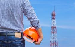 设计拿着与天线电信塔柱子的黄色安全帽 免版税图库摄影