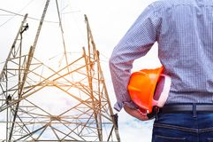 设计拿着与工作在定向塔建筑塔的电工的黄色安全帽 免版税库存图片