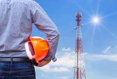 设计拿着与电信塔柱子的安全帽 库存照片