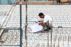 设计检查在建造场所的一张图纸 免版税库存图片