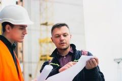 设计谈的谈论与建筑师与体系结构计划的图纸一起使用,速写项目 免版税图库摄影