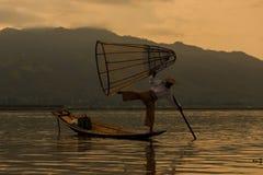 设陷井有一条小船的渔夫在缅甸的Inle湖 库存照片