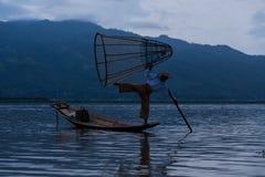 设陷井有一条小船的渔夫在缅甸的Inle湖 免版税库存图片