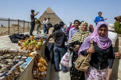 访客向吉萨棉在Khafre金字塔的基地附近聚集在开罗,埃及 免版税库存照片