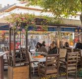 访客在一个街道咖啡馆坐在雨天在锡比乌市在罗马尼亚 免版税库存图片