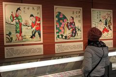 访客在中国国家图书馆里查找在陈列的中国的传统新年度绘画 免版税库存照片